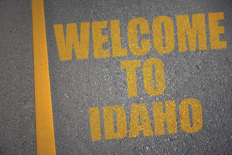 asphalt road with text welcome to idaho near yellow line.